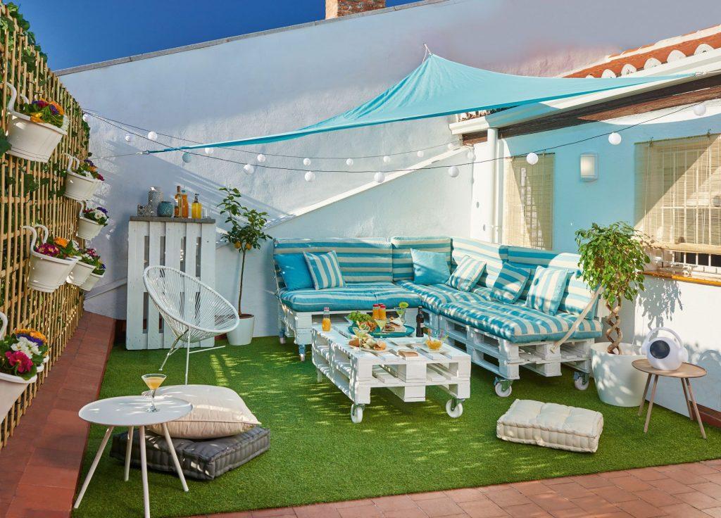 Terraza urbana estilo chill out con luces y césped artificial